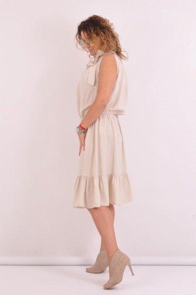 Sukienka beżowa wiązana przy szyi.